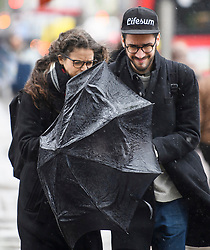 © Licensed to London News Pictures. 30/04/2018. London, UK. A couple battle with their umbrella in windy and wet conditions on Kensington High Street in West London as parts of the UK are expected to experience an average months rain in 24 hours. Photo credit: Ben Cawthra/LNP