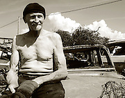 Bratislava, Slovakia (June 13 2006) .Jano 66, sits on the hood of an old car reflecting on the cities future. Jano lives in an old bus at the edge of the city making his living recycling scrap meta for cash..**Heavy Metal Lifestyle.