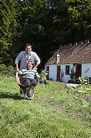 Father pushing son (7-9) in wheelbarrow outside cottage