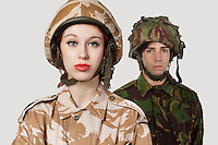 Portrait of young woman and man in military clothes against gray background