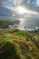 Late in the afternoon the sun takes a final peek through the clouds to light up the grassy coast of Northern Ireland in in the Causeway region. Portrush, Northern Ireland.