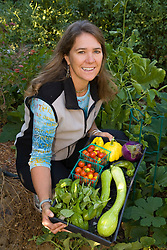 United States, California, Stockton, woman in garden holding harvest of vegetables MR