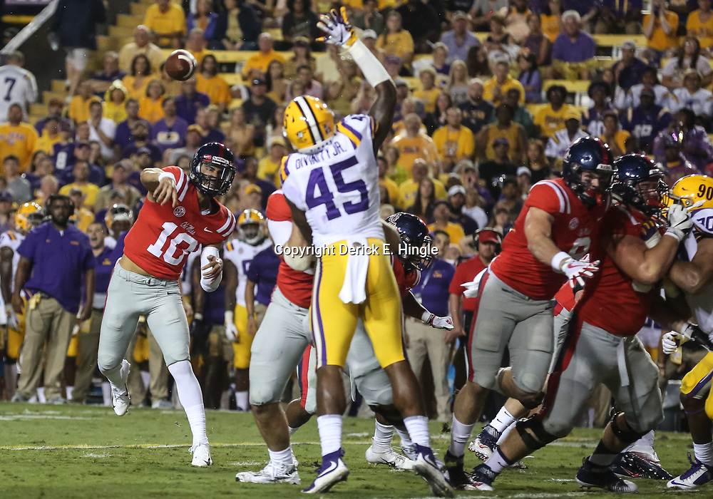 Sep 29, 2018; Baton Rouge, LA, USA; Mississippi Rebels quarterback Jordan Ta'amu (10) throws past LSU Tigers linebacker Michael Divinity Jr. (45) during the first quarter of a game at Tiger Stadium. Mandatory Credit: Derick E. Hingle-USA TODAY Sports