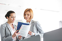 Young businesswomen discussing over book in office