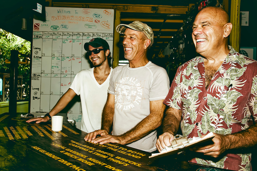 Three Bananarama Resort dive shop employees pose in shop after dive, in Roatan, Honduras. Copyright 2010 Reid McNally.