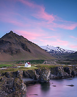 Arnarstapi at sunrise, Mount Stapi and Snæfellsjökull glacier in background. Snæfellsnes Peninsula, West Iceland.