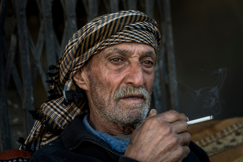 75-year-old Kasim Yahia Ali Hussein smokes a cigarette outside an abandoned building in the Old City of Mosul where he has lived all his life. Since the end of the battle against Islamic State in Mosul Kasim has been tasked with keeping watch over destroyed stores and warehouses that belong to his neighbours. <br />