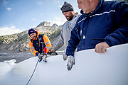 Climate | Albedo | Rhone: Ramon Cirani, Ghirardi Francesco and Gritti Emanuele stitch together huge fleece blankets to prevent the popular ice tunnel at the mouth of the Rhone Glacier from melting. After a winter with record amounts of snow, most of it was gone when this image was taken on July 14th 2018, exposing the darker ice. While snow is a brilliant reflector of the energy from the sun, the darker ice absorbs the energy instead, accelerating the melting of the glacier. The color and darkness of glacier ice vary all over the world, depending on build-up of pollution, age of the ice, particles picked up by the ice and by microorganisms in the ice. The glacier ice is however rarely white as snow. With shorter winters and vanishing snow cover, the melting of the glaciers is accelerating.<br /> <br /> The Rhone Glacier (pictured) now melts more than 70 centimeters in thickness every week in the summer months. Between 1996 and 2006, an estimated 0.9 billion cubic metres of water melted yearly from the Swiss glaciers. That number is likely much higher today. Switzerland just had the hottest July since 1864, it has the lowest rainfall since 1921, and the rivers are running at record low levels. The covering of the glacier is the idea of Philipp Carlen, who owns and operates an ice cave at the mouth of the glacier. The glacier is still melting, but by covering it with blankets, he is able to attract tourists who are coming to see the dying glacier.
