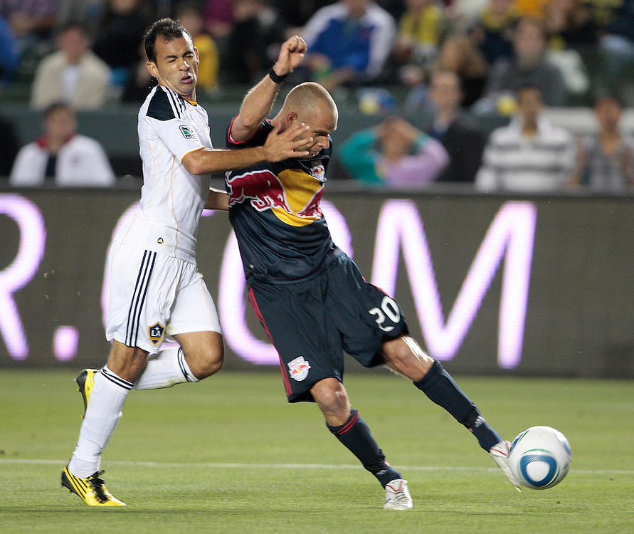 New York Red Bulls midfielder Joel Lindpere, right, of Estonia shoots the ball defended by Los Angeles Galaxy midfielder Juninho of Brazil during the first half of a MLS soccer match, Saturday, May 7, 2011, in Carson, Calif. (AP Photo/Jason Redmond)
