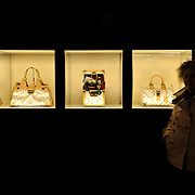 A woman standing by the display of Louis Vuitton bags in Grafton Street, Dublin.