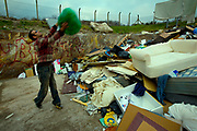A man throwing rubbish on a rubbish tip.
