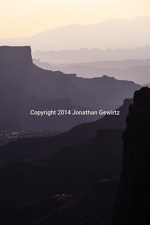 Morning view of Shafer Canyon backlit in hazy sunshine, Canyonlands National Park, Utah.<br />