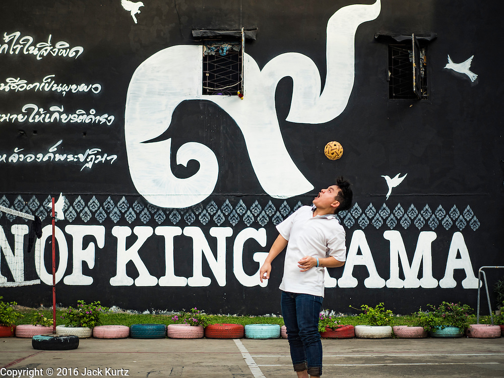 """01 DECEMBER 2016 0 BANGKOK, THAILAND: Men play takraw in Chalermla Park (Graffiti Park) in Bangkok. The east wall of the park was repainted with a large mural that says """"Born in the reign of King Rama 9,"""" with the nine written in Thai script. Bhumibol Adulyadej, the Late King of Thailand, was known as Rama 9. The park was repainted in his honor after his death on Oct 13.    PHOTO BY JACK KURTZ"""