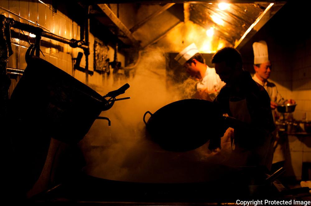 Cooks working in a steamy kitchen in Chengdu