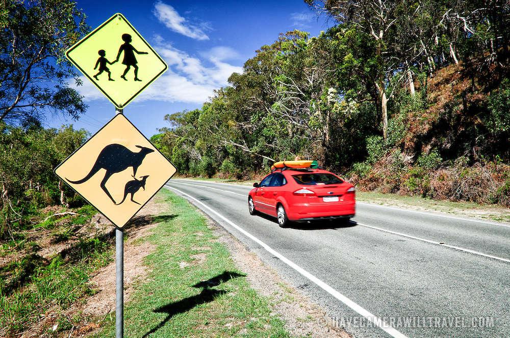 Kangaroo crossing warning sign modified with a joey to mirror the standard children crossing sign on Stradbroke Island, Queensland, Australia North Stradbroke Island, just off Queensland's capital city of Brisbane, is the world's second largest sand island and, with its miles of sandy beaches, a popular summer holiday destination.