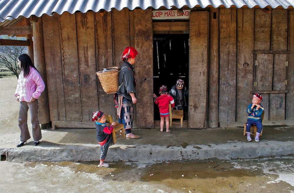 Outside a school building in a red Hmong village near Sa Pa, North Vietnam.  Four toddlers and a mother, all in traditional clothing, carry little chairs into the doorway.  Their teacher, in contemporary clothing of pants and a pink down jacket, stands idly by.  The school building is traditionally constructed from vertical wooden planks abutting each other.