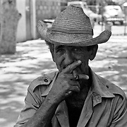 A Cuban man relaxes with a cigar in a park in Havana.