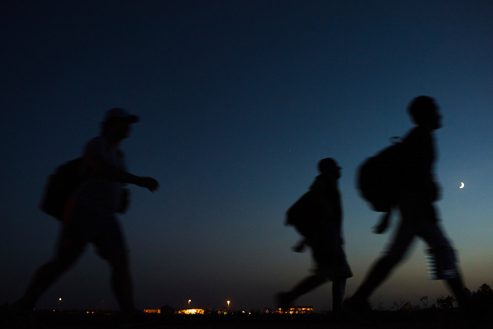 Migrants walk through fields, circumventing official checkpoints, from the Serbian to the Croatian border on September 17, 2015.