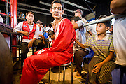 02 JULY 2006 - PHNOM PENH, CAMBODIA: A boxer waits for his bout to begin during a traditional Khmer boxing match in Phnom Penh, Cambodia. Khmer boxing is the same sport as Muay Thai (traditional Thai kick boxing) but because off animosity between Thailand and Cambodia it is called Khmer Boxing in Cambodia. The Cambodians claim to have invented the sport, which is also practiced in Laos and Burma. Photo by Jack Kurtz