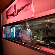 Chef Danny Bowien works in the kitchen of his restaurant, Mission Chinese, underneath a poster of Michael Jordan hanging in the hallway at the restaurant's New York City location on the Lower East Side of Manhattan on Tuesday, July 31, 2012 in New York, NY..
