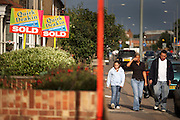 A young family walk gloomily past property Sold signs in a street at Grays, Essex England. Passing the prominent signs that bear the name of Quirk Deakin, a local estate agent in the industrial towns of south Essex and the Thames Gateway, is the location for dramatic increases of new housing developments. Both the parents and their daughter look depressed in this time of economic recession, when families are having their homes repossessed after defaulting on mortgage repayments. It is a bright summer day in Grays, east of the capital, just outside of the M25 orbital motorway and on the Thames river.