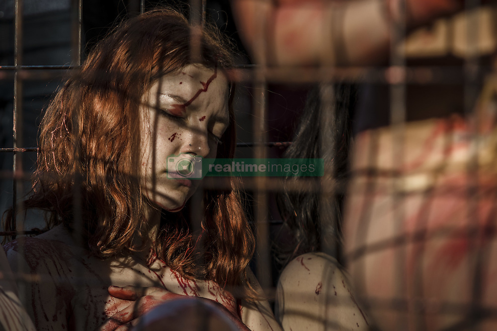 December 11, 2016 - Naked animal rights activists covered with fake blood crouch in a cage during one of the most impacting animal rights protests staged in Barcelona to denounce the use of animal skins and fur (Credit Image: © Matthias Oesterle via ZUMA Wire)