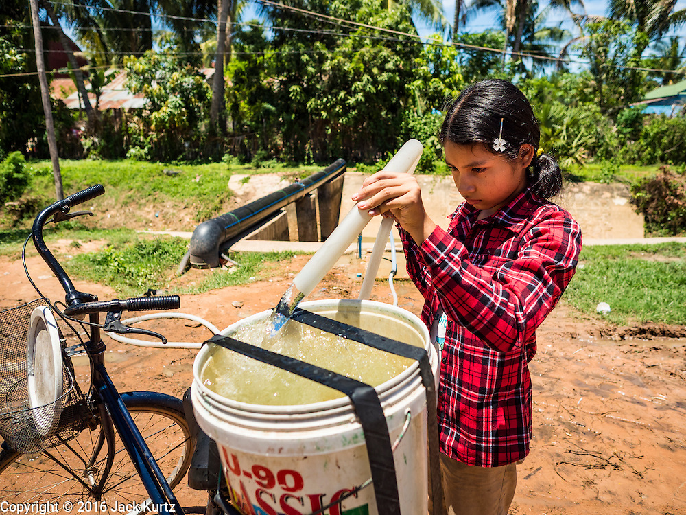 02 JUNE 2016 - SIEM REAP, CAMBODIA: A girl fills a bucket of water on her bike at a public well west of Siem Reap. She said the well near her home had no more water and now she spent her days riding her bike from her home to the well, filling the bucket, riding home and then repeating the process. Some days she had to stay home from school to get water for her family. Cambodia is in the second year of  a record shattering drought, brought on by climate change and the El Niño weather pattern. Farmers in the area say this is driest they have ever seen their fields. They said they are planting because they have no choice but if they rainy season doesn't come, or if it's like last year's very short rainy season they will lose their crops. Many of the wells in the area have run dry and people are being forced to buy water to meet their domestic needs.       PHOTO BY JACK KURTZ
