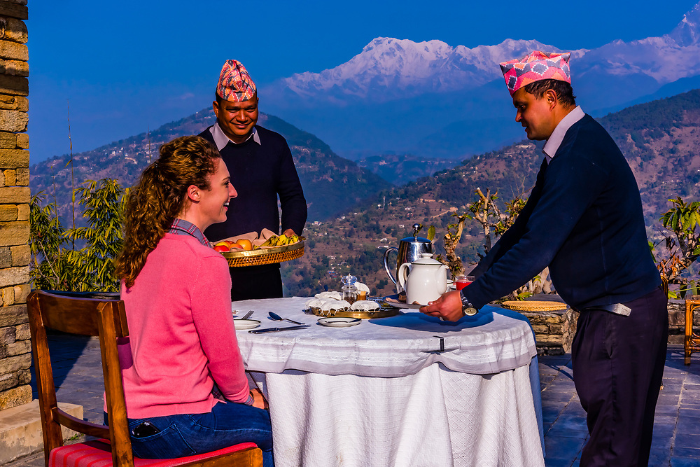 Breakfast served on the patio of the Tiger Mountain Pokhara Lodge with three peaks of the Annapurna Massif (Annapurna South, Annapurna 1 and Hiunchuli) in the background.  Lekhnath, near Pokhara, Nepal.