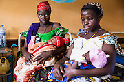 Two mothers with their children sit and wait for the doctors during the morning ward round  at St Walburg's Hospital, Nyangao. Lindi Region, Tanzania.