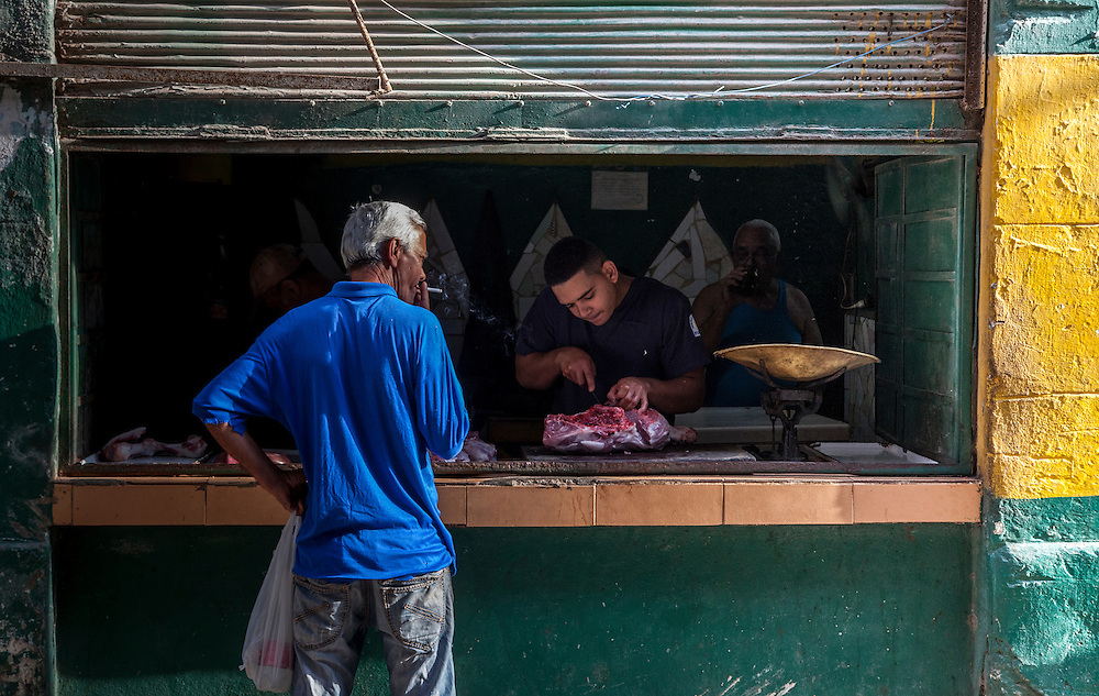 A Cuban Butcher in Old Towne Havana prepares a citizens weekly ration. <br /> <br /> All of my prints are available, custom framed by me,  in my Etsy Store.