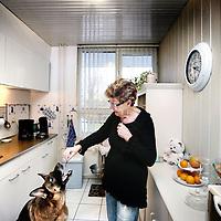 Nederland, Amsterdam , 11 december 2012..Mevrouw Stoekenbroek voert haar hond in haar keuken van haar appartement in amsterdam noord..Links de verouderde geiser die in de 40 jaar dat mevr Stoekenbroek haar woning huurt slechts 1x vervangen is en rechts de koolmonoxidemeter..Koolmonoxidevergiftiging. Na vele soms fatale ongevallen vrezen bewoners van huizen met geisers.Vele huurders in Amsterdam hebben klachten hieromtrent. Woningcooperaties doen te weinig om geisers te vervangen..Foto:Jean-Pierre Jans
