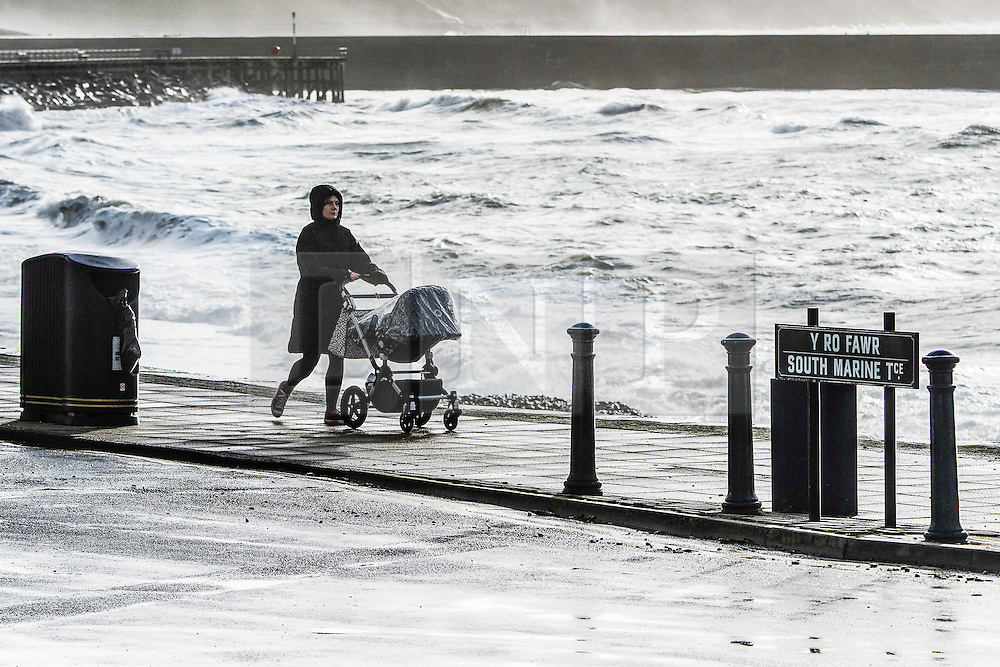 © London News Pictures. 22/12/2016. Aberystwyth, UK. A woman pushes a pram along the coastline as Waves batter the seafront and harbour wall at Aberystwyth as Storm Barbara clips the the Cardigan Bay coast of the Irish Sea. Strong winds and damp weather are due to hits the west coast and northern parts of the UK over the Christmas period.  Photo credit: Keith Morris/LNP