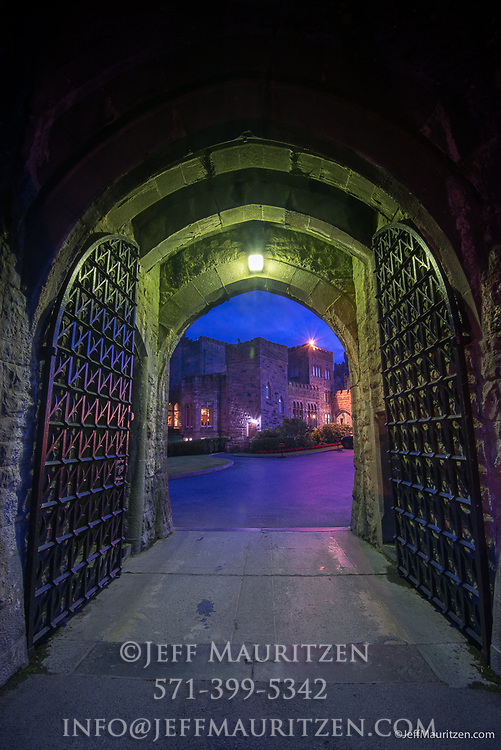 Gates lit up at night, lead into Ashford Castle, a 13th century castle turned into a 5 star luxury hotel.