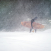 "Aurelien treks across the snow in near white-out conditions heading towards the open water of Lake Ontario. ""It really gets nasty, it gets extremely nasty, it gets extremely windy, and extremely cold. There is no visibility and that's when we have to surf because that's when there are waves. We are not talking about a groundswell, we are talking about a wind swell. Most of the time the windy day's come in the middle of winter."""