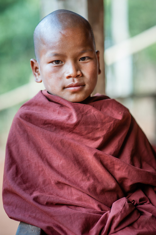 Novice Buddhist monk wrapped in his maroon robe (Myanmar)