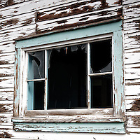 Broken window pane and peeling paint at a structure in a Colorado ghost town
