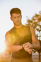 Portrait of young attractive man looking at his wristwatch in park with lens flare