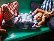 05 JUNE 2014 - YANGON, YANGON REGION, MYANMAR: A child rests in his father's lap while they ride the Yangon Circular Train. The Yangon Circular Train is a commuter train that circles Yangon, Myanmar (Rangoon, Burma). The train is 45 kilometers long, makes 38 stops and takes about three hours to make a loop of the city.     PHOTO BY JACK KURTZ