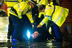 "© Licensed to London News Pictures . 22/12/2018 . Manchester , UK . Police detain a man after a fight breaks out outside The Birdcage nightclub on Withy Grove . Revellers out in Manchester City Centre overnight during "" Mad Friday "" , named for historically being one of the busiest nights of the year for the emergency services in the UK . Photo credit : Joel Goodman/LNP"