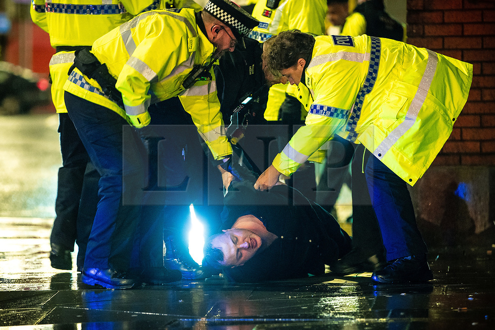 """© Licensed to London News Pictures . 22/12/2018 . Manchester , UK . Police detain a man after a fight breaks out outside The Birdcage nightclub on Withy Grove . Revellers out in Manchester City Centre overnight during """" Mad Friday """" , named for historically being one of the busiest nights of the year for the emergency services in the UK . Photo credit : Joel Goodman/LNP"""