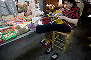 A woman knits a sweater as she sells spices and Chinese traditional medicine in a market in Longnan, China.