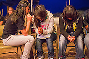 "13 JULY 2012 - FT DEFIANCE, AZ: Teenagers pray during the alter call at the 23rd annual Navajo Nation Camp Meeting in Ft. Defiance, north of Window Rock, AZ, on the Navajo reservation. Preachers from across the Navajo Nation, and the western US, come to Navajo Nation Camp Meeting to preach an evangelical form of Christianity. Evangelical Christians make up a growing part of the reservation - there are now more than a hundred camp meetings and tent revivals on the reservation every year. The camp meeting in Ft. Defiance draws nearly 200 people each night of its six day run. Many of the attendees convert to evangelical Christianity from traditional Navajo beliefs, Catholicism or Mormonism. ""Camp meetings"" are a form of Protestant Christian religious services originating in Britain and once common in rural parts of the United States. People would travel a great distance to a particular site to camp out, listen to itinerant preachers, and pray. This suited the rural life, before cars and highways were common, because rural areas often lacked traditional churches.  PHOTO BY JACK KURTZ"