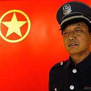 Policeman and chinese flag near Huaihai Lu, Shanghai, China, Asia