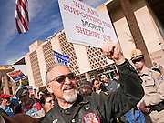 23 JANUARY 2012 - PHOENIX, AZ:     Vince Ansel (CQ) protests in support of SB 1070 and was surrounded by anti-1070 protesters at the State Capitol Monday, Jan 23. Both sides of the immigration debate congregated on the capitol grounds to protest against and in favor of SB 1070 and other anti immigration bills. At the same time people were protesting, legislators from both sides of the issue held press conferences.   PHOTO BY JACK KURTZ