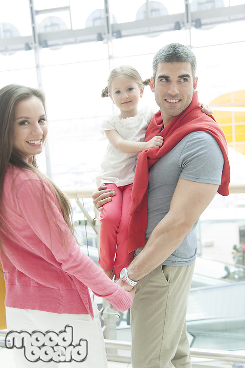Father holding young daughter up at waist height and holding hands with mother
