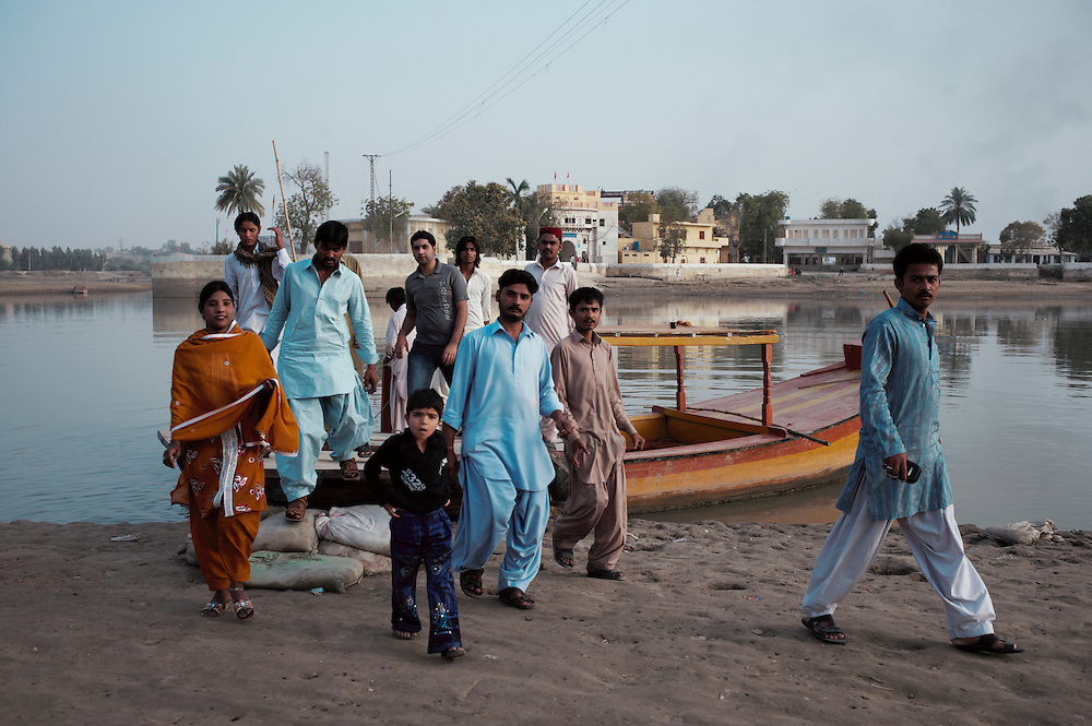 Passengers disembark a boat at Sadhu Bela, a Hindu temple on the Indus River, Sukkur, Sindh province, Pakistan on March 23, 2012. A rise in in reports of forced conversion of Hindu girls to Islam in provinces in Pakistan has gained prominence within the political, media, religious and social domains with the case of a 21 year old woman Rinkle Kumari. On February 24, 2012 her family reported to police of Ghotki district, Sindh province that she had been abducted by armed men from the family home in the village of Mirpur Mathelo. it is then alleged by the family and broadrer hindu community that she was forced to convert to Islam and marry Syed Naveed Shah, a neighbour of the girl within their village. Complications with court hearings for the case, perceptions by the Muslim community that the police sided with the Muslim community when dealing with issue and the politicisation of the case by a Pakistan Peoples Party Member for National Assembly Mian Abdul Haq alias Mian Mitho has led to a hearing being called in the Supreme Court, Islamabad, Pakistan on March 26, 2012. The hearing will hopefully ascertain whether the girl was abducted or in fact left with Syed Naveed Shah of her own free will.