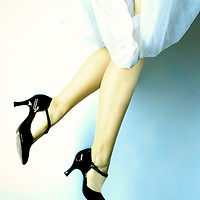 A young woman wearing a white dress and black shoes