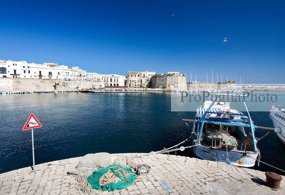 Città vecchia e castello angioino davanti ad una paranza ormeggiata nel porto di Gallipoli (LE)