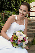 Mid adult woman wearing white dress holding bouquet smiling