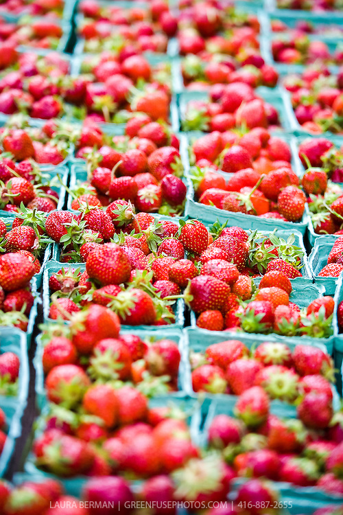 Bright red strawberries in blue pint baskets at a farmers market.